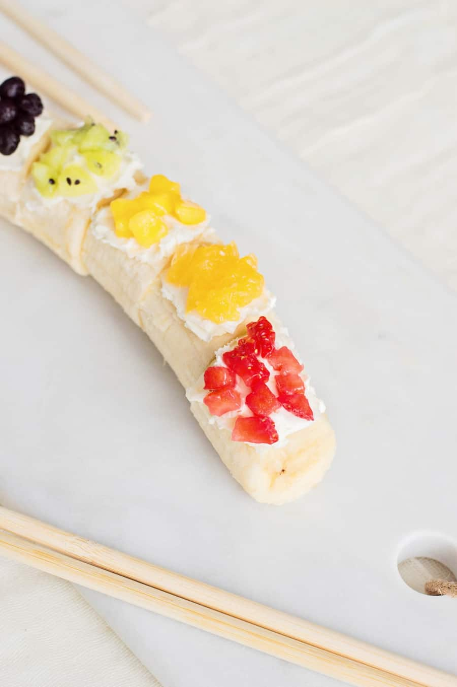 Kids will love getting a healthy, vitamin-packed start to their day with this rainbow fruit banana sushi - a fun snack featuring fresh fruit!