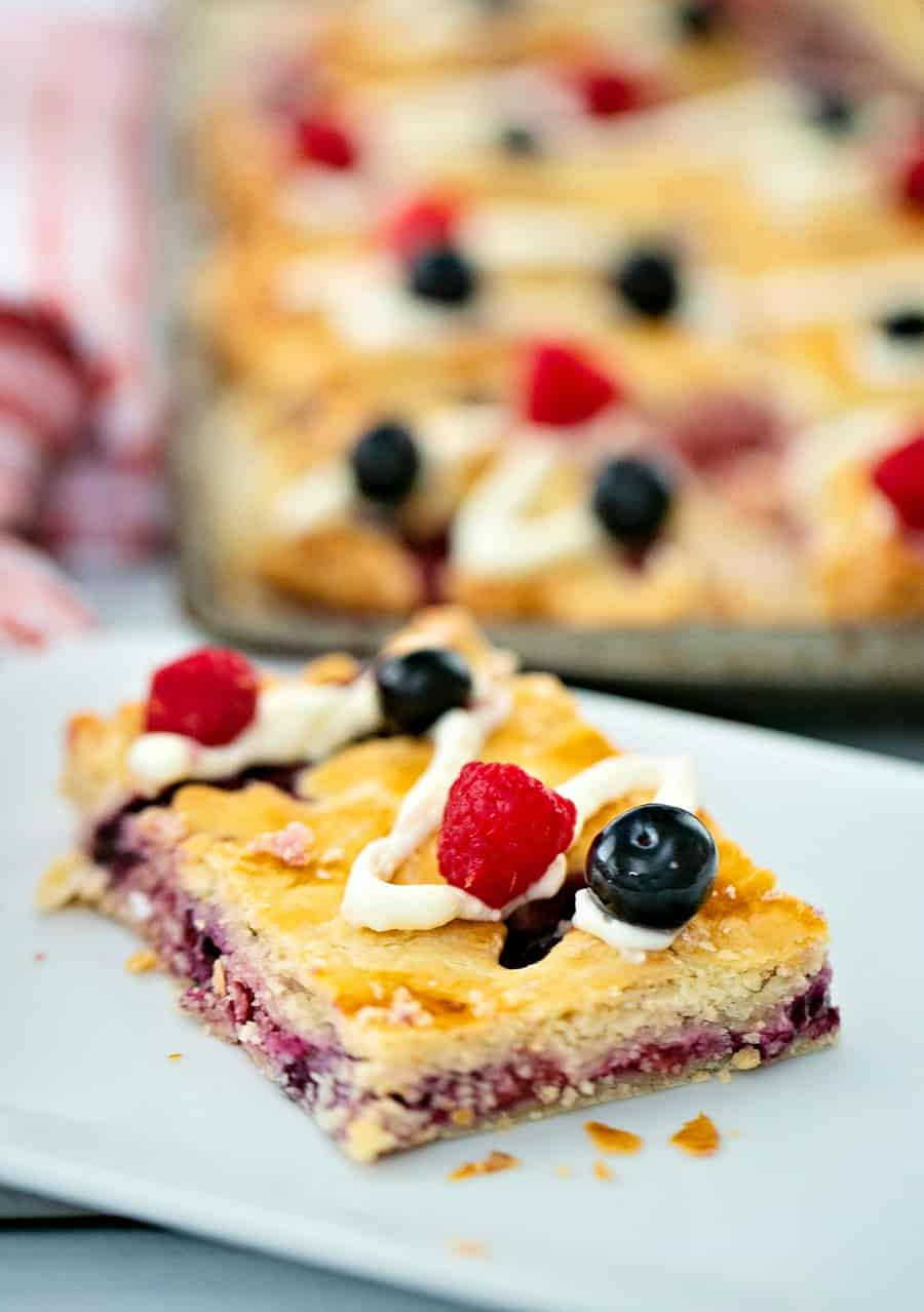 Raspberry Blueberry Slab Pie with a cream cheese frosting drizzle garnished with fresh berries. Delicious and easy patriotic dessert for Memorial Day or Fourth of July.