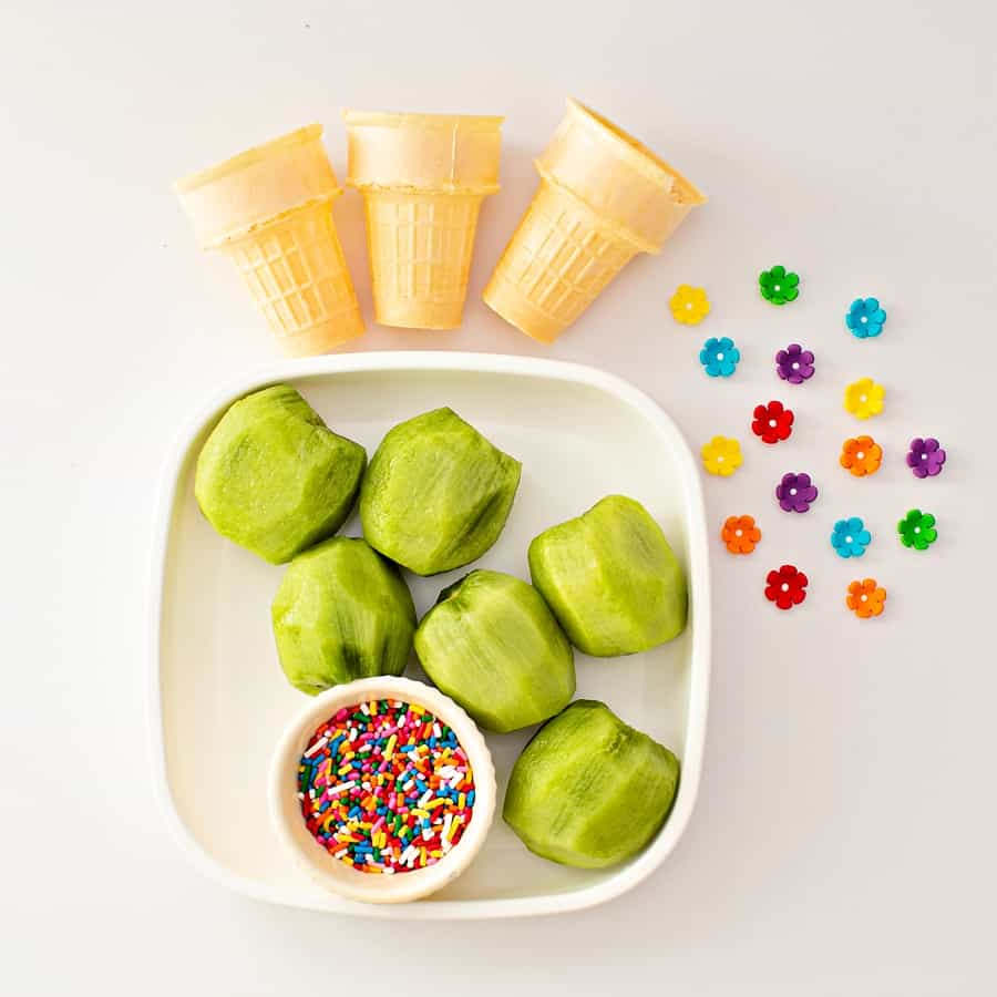 Peeled kiwi fruit with ice cream cake cones and sprinkles