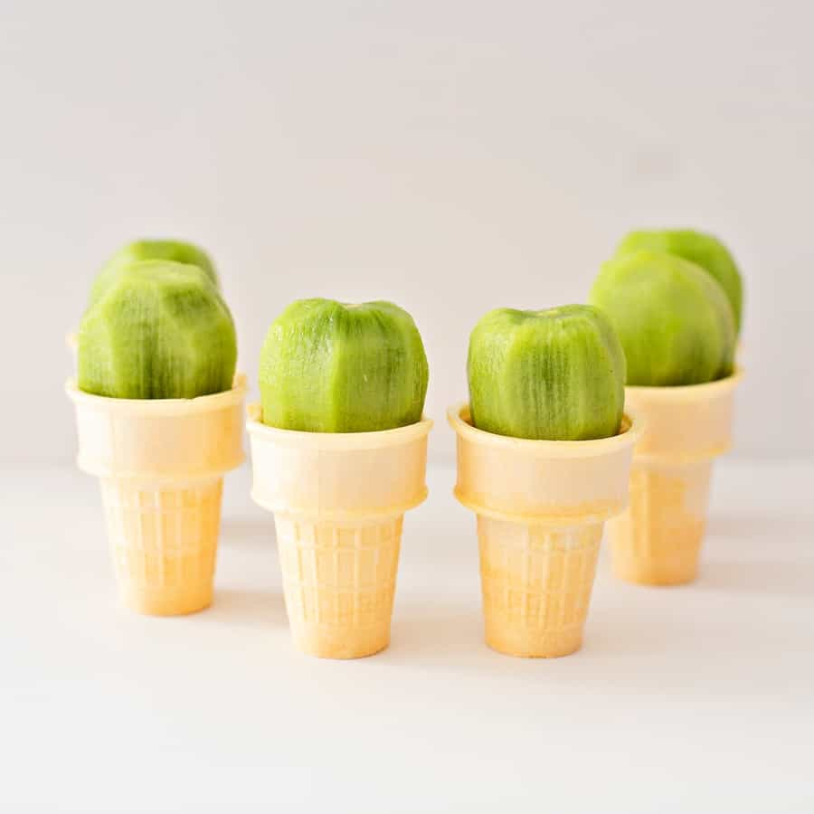 peeled kiwi fruit on top of ice cream cake cones