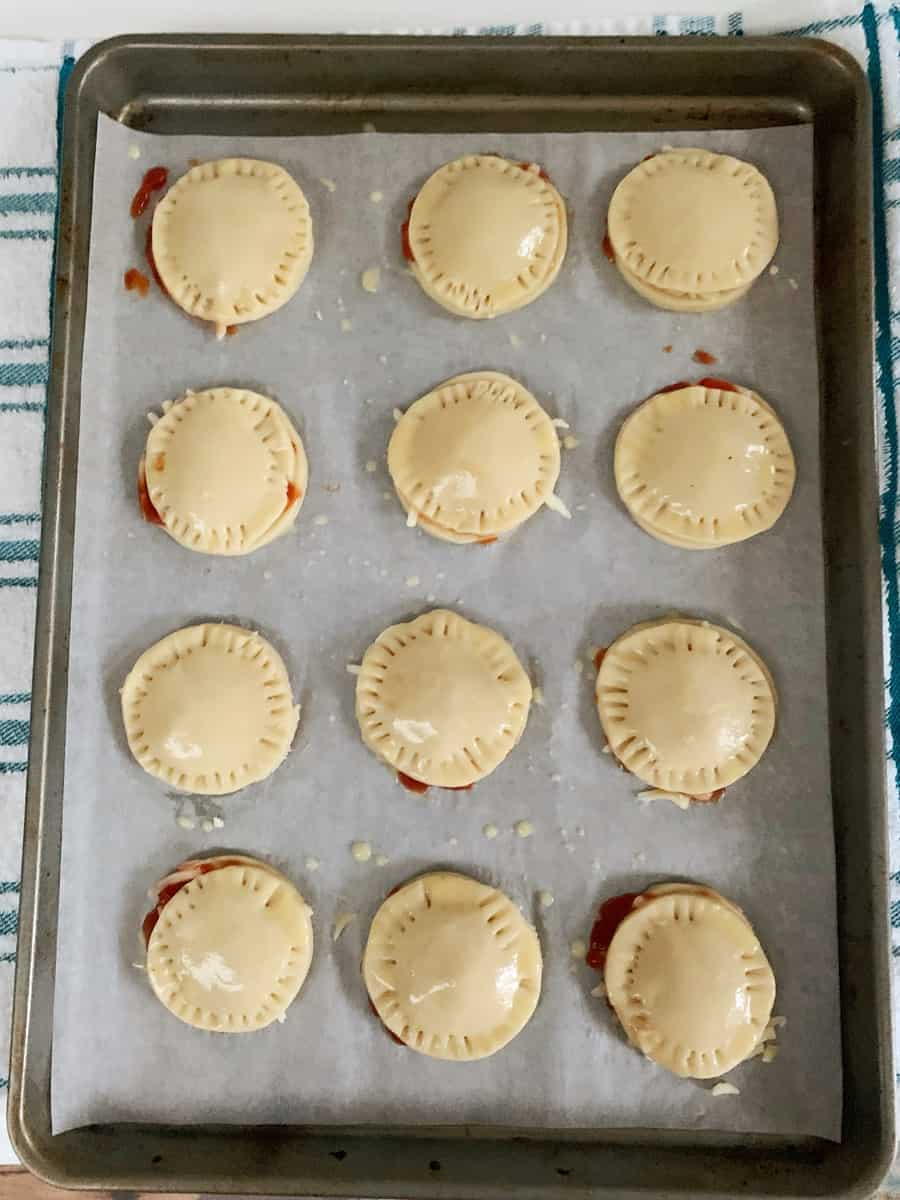 mini hand pie pizza on a baking sheet