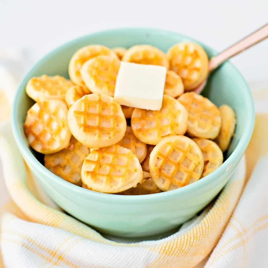 mini waffles in a blue green bowl with a pat of butter on top with a pink spoon inside
