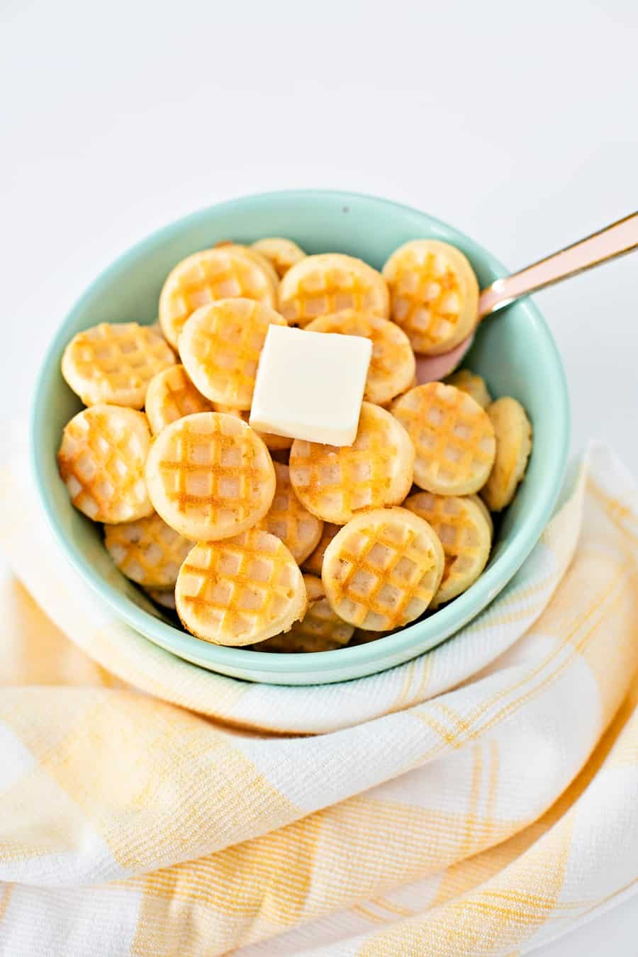 Waffle pancake cereal. Mini waffles in a bowl with a pat of butter.