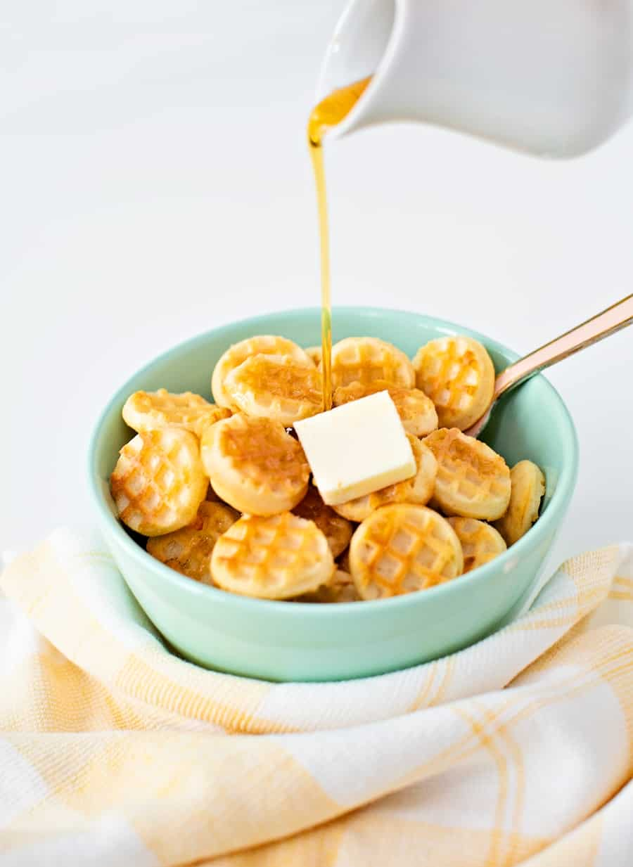 syrup being poured over mini waffle pancake cereal in a bowl