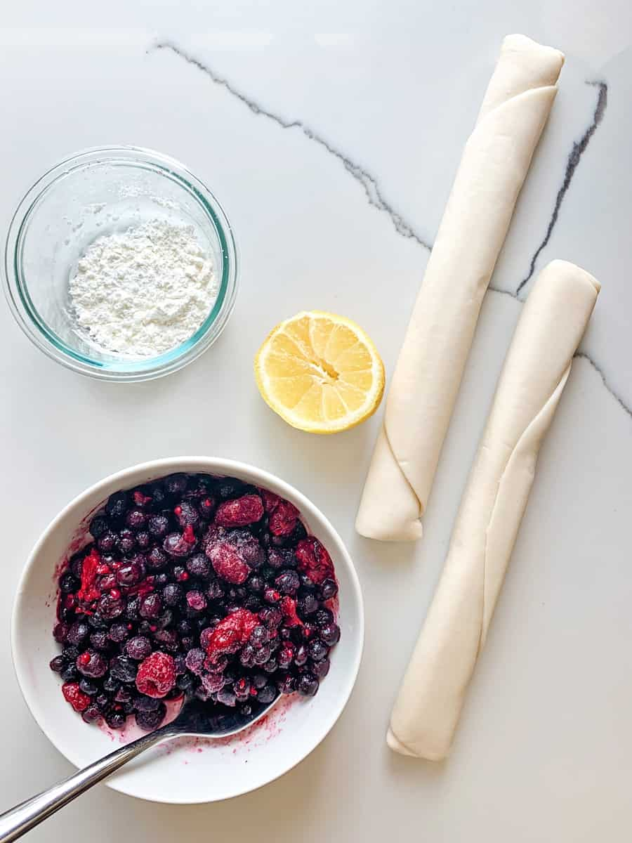 berries in a bowl with a lemon and rolled pie crust