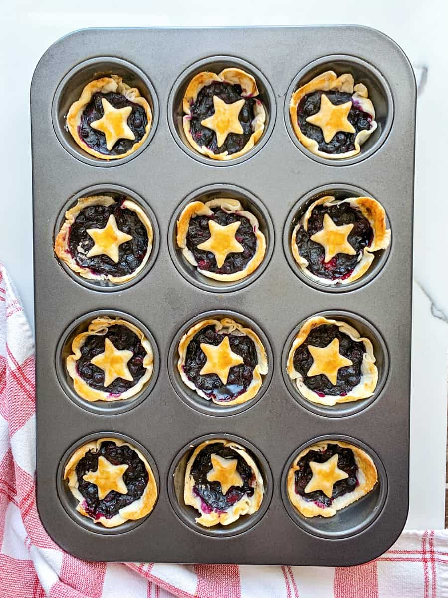 baked mini berry pies in a muffin tin with star pie dough over them