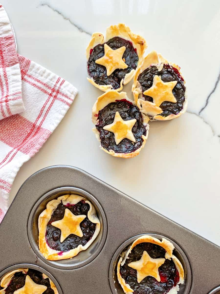 mini berry pies in a muffin tin with pie dough stars over them