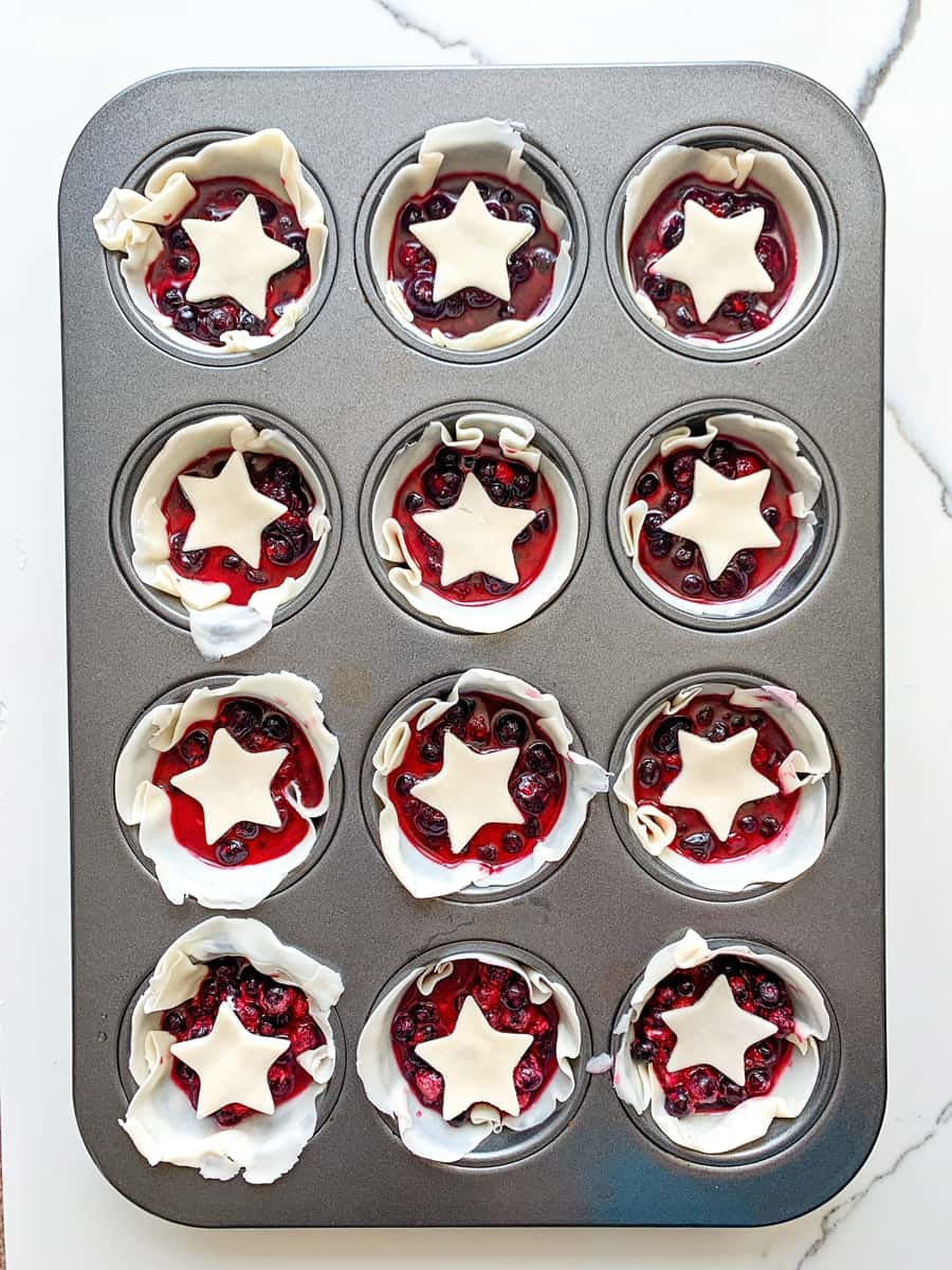 mini berry pies in a muffin tin with star pie dough over them
