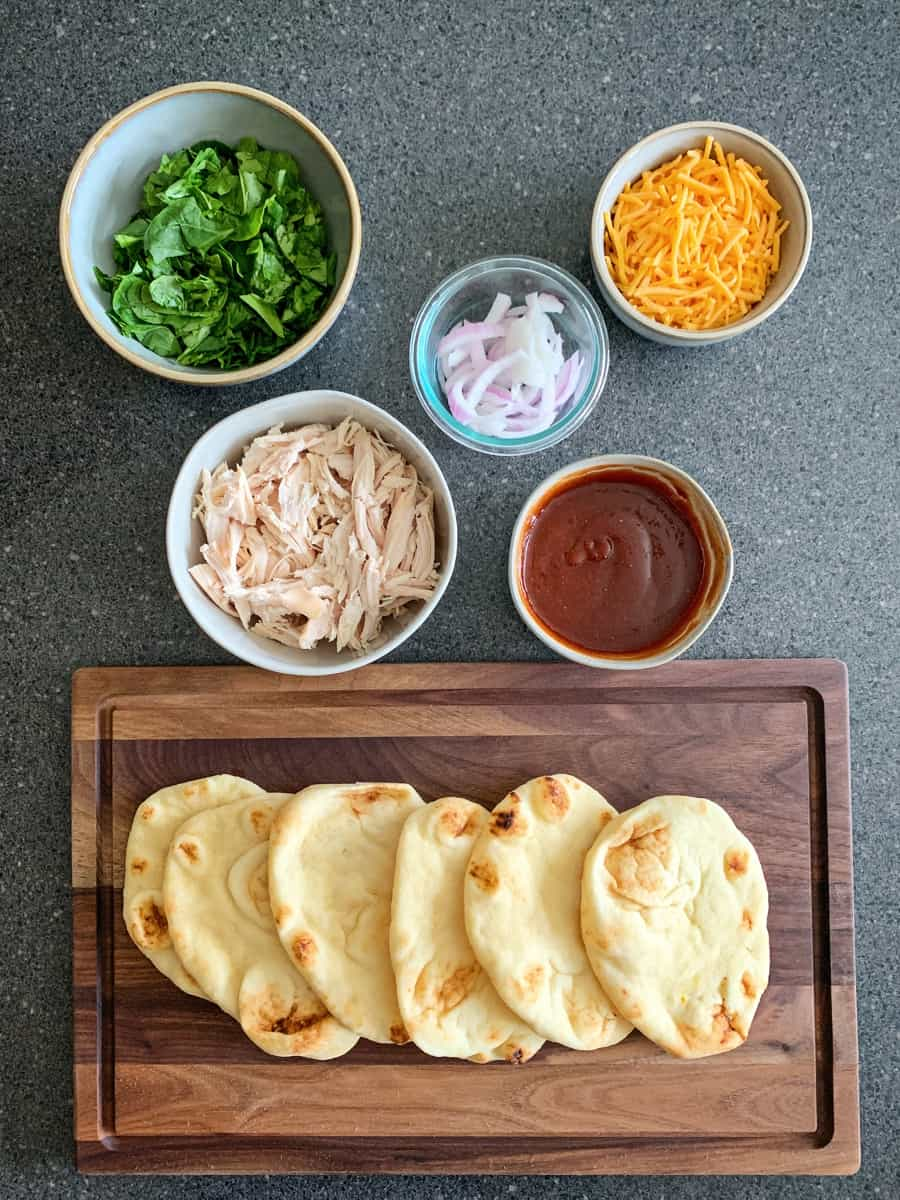 mini naan bread with toppings like chicken, spinach, cheese, bbq sauce and onions