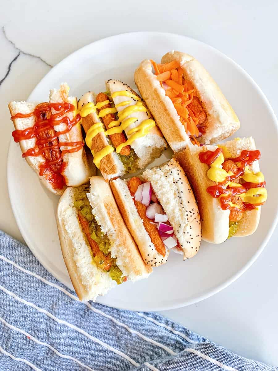 carrot hot dogs on sliced half buns with various hot dog toppings like mustard, ketchup and relish