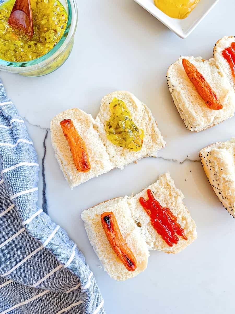 sliced hot dog buns in half with carrots inside and relish