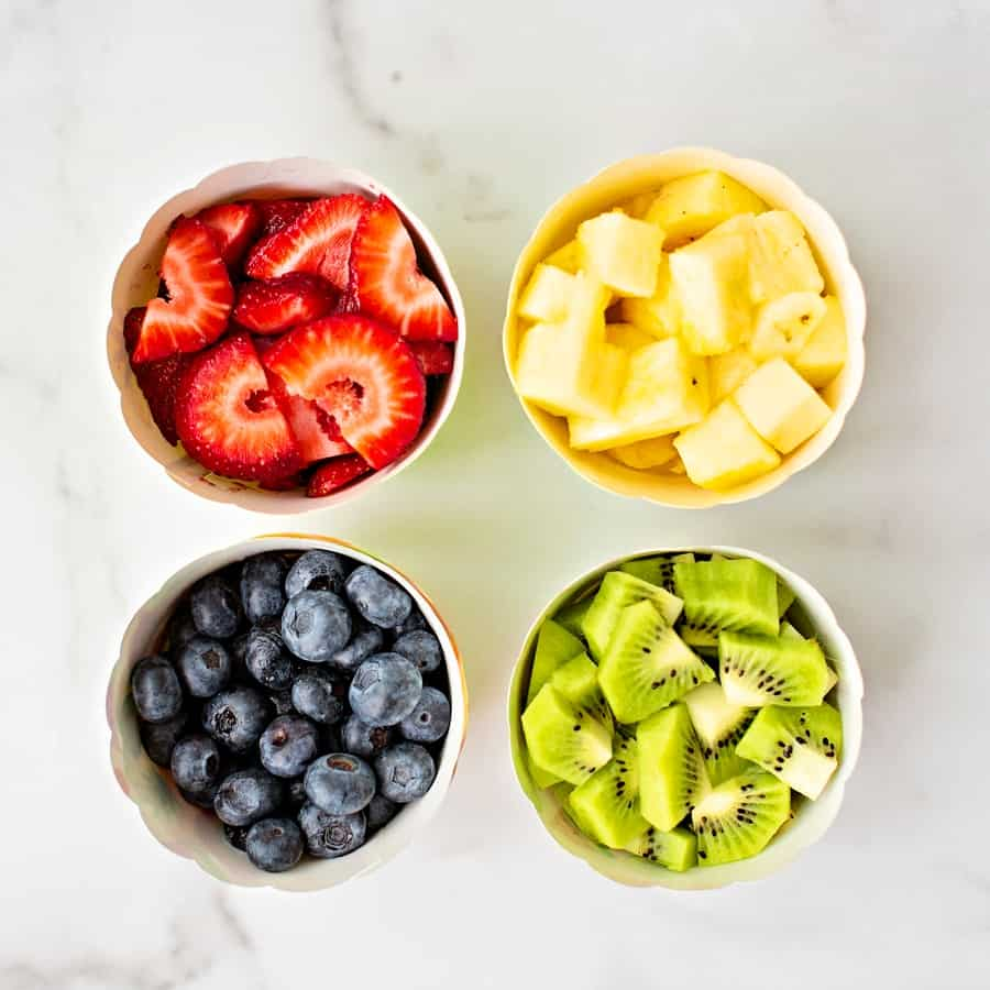 bowls of fruit blueberries, kiwi, pineapple and strawberries up up close