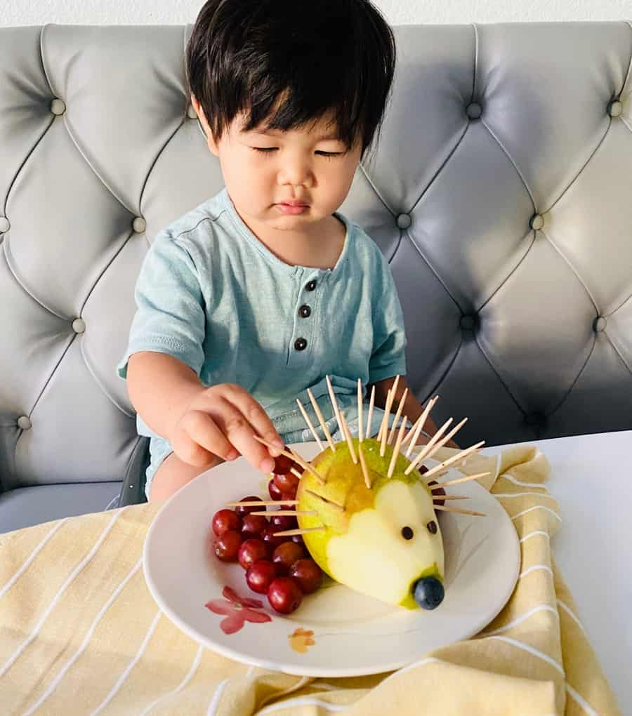 toddler boy practicing fine motor skills on a pear hedgehog made of grapes