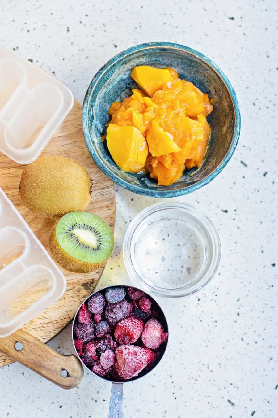 ingredients to make fresh fruit mango popsicles like pureed mango, frozen berries and kiwi fruit