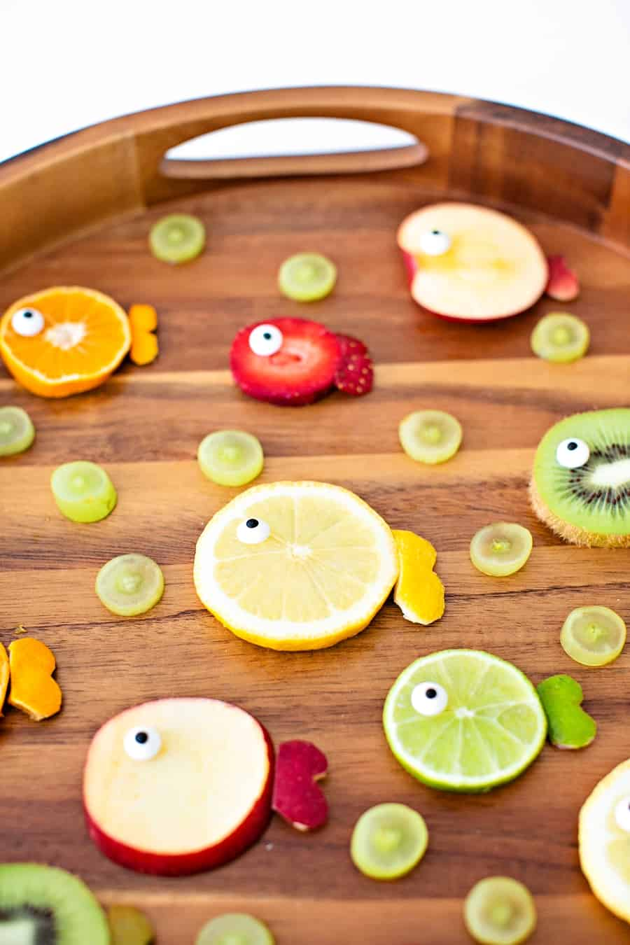 oranges, limes, kiwi and apples cut to resemble fish fruit for a kid snack