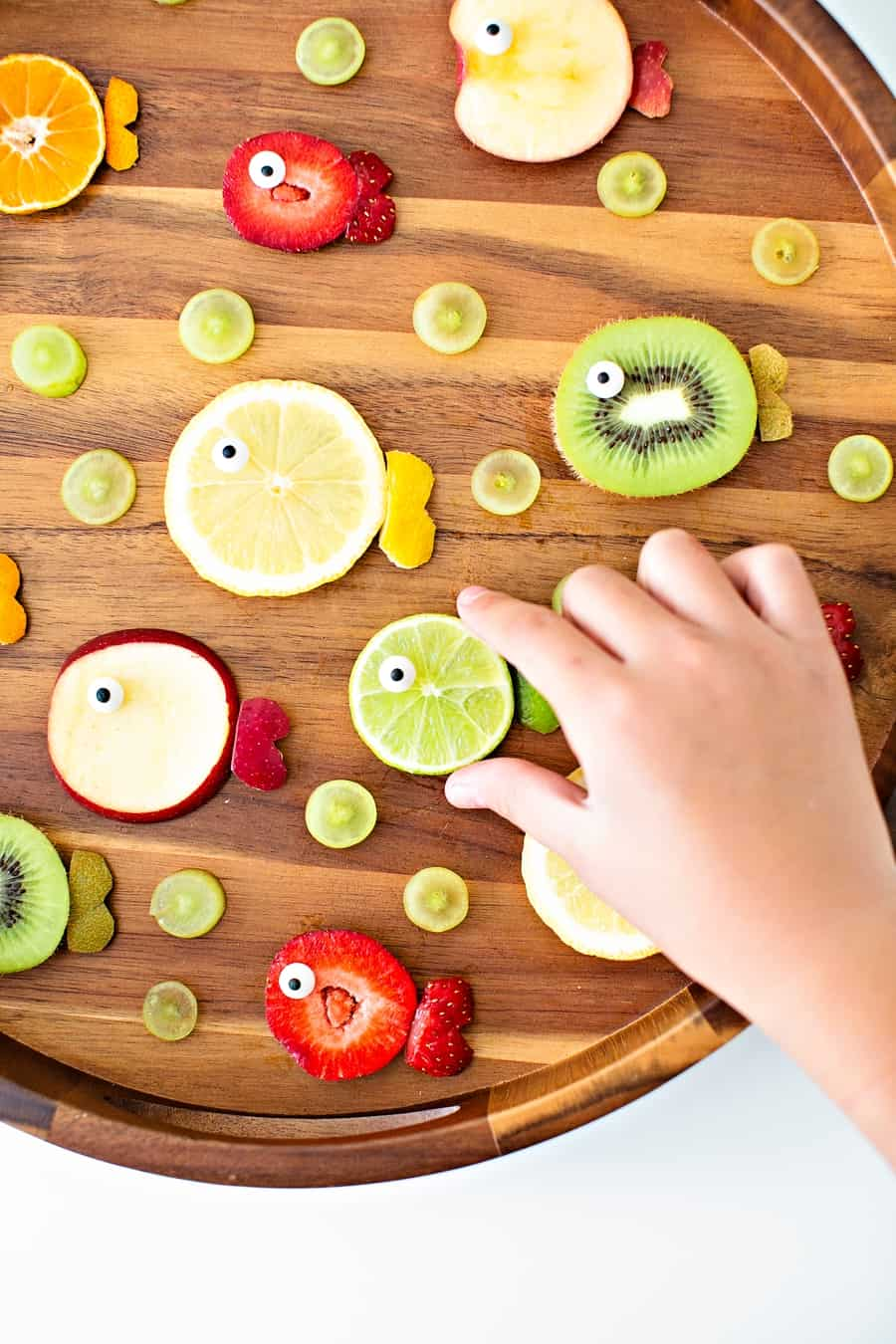 strawberries, oranges, limes, kiwi and apples cut to resemble fish fruit for a kid snack