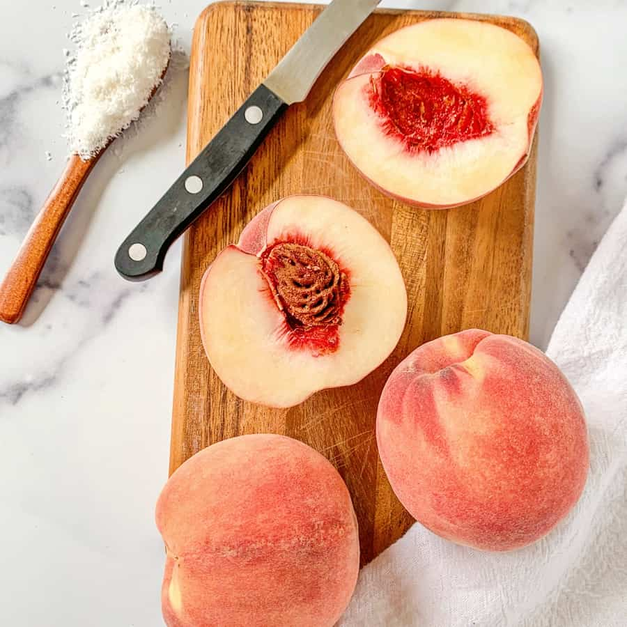 cut peaches on a wooden cutting board