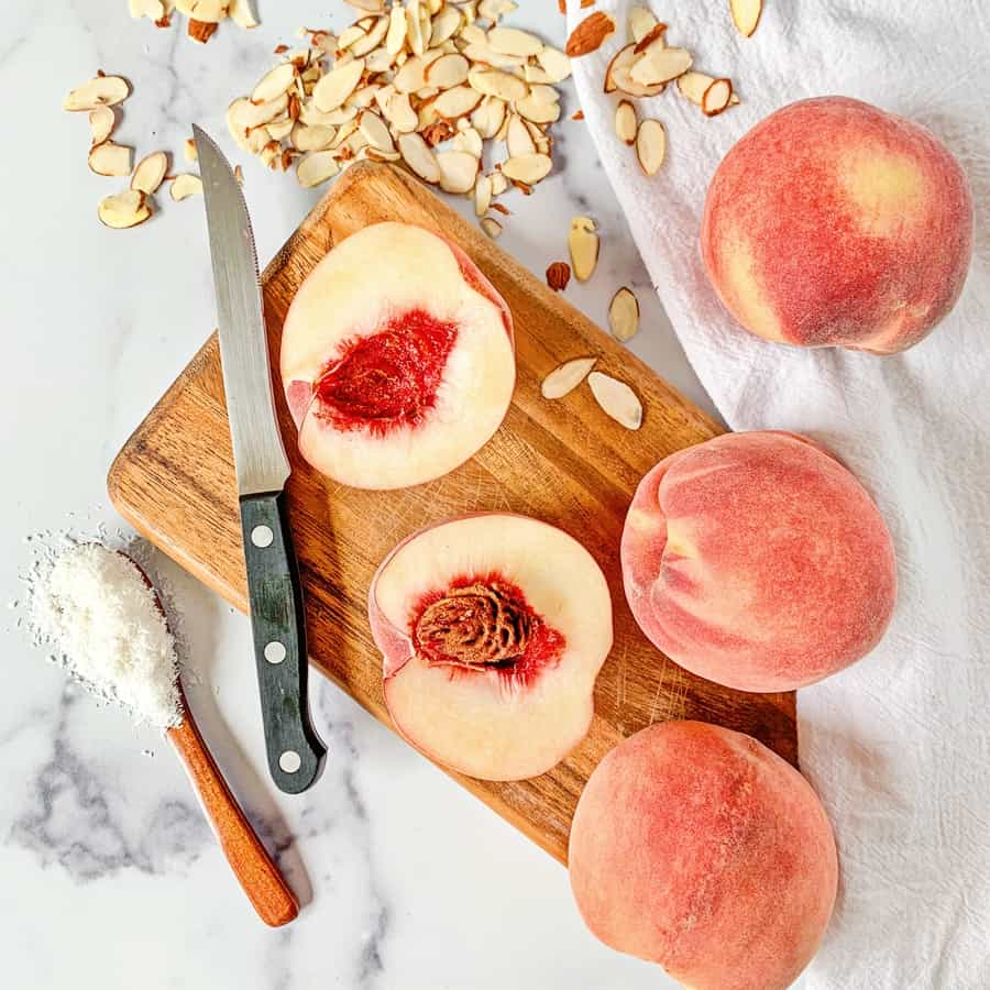 cut peaches on a wooden cutting board with almonds and coconut