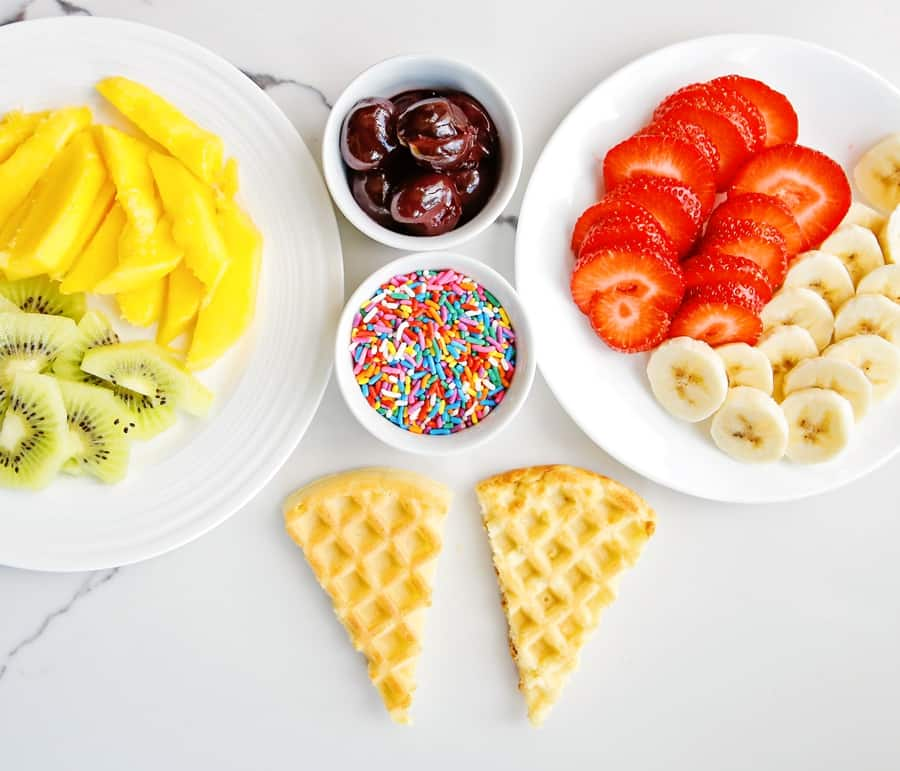 sliced fresh fruit, sprinkles and waffles cut into cones to make ice cream cone waffles
