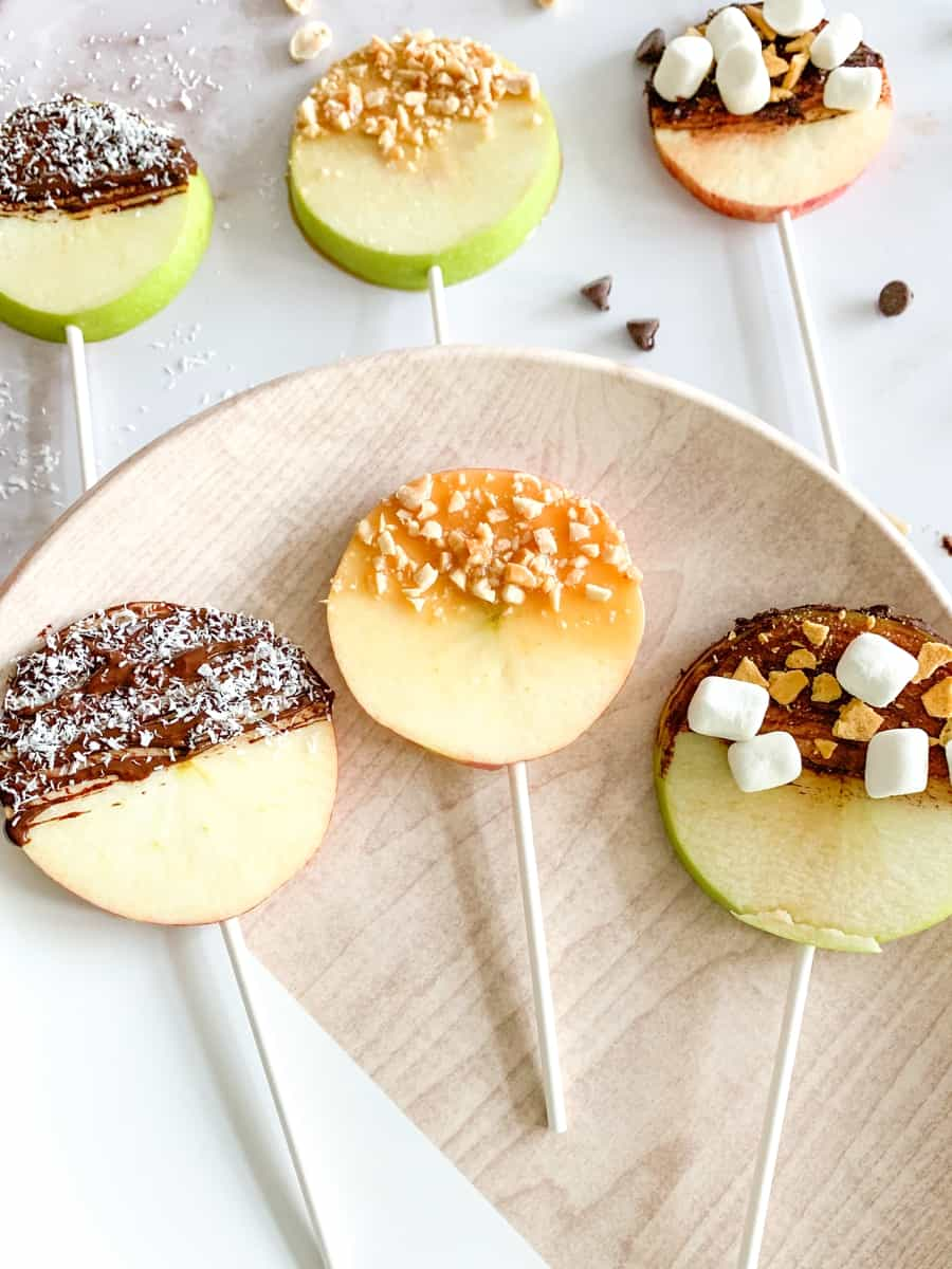 apple fruit lollipops. sliced apples with lollipop sticks and various chocolate, caramel and nut toppings